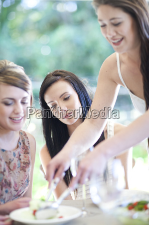 young woman serving meal to friends