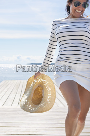 young woman holding sunhat