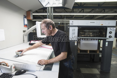 worker preparing digital printing equipment in