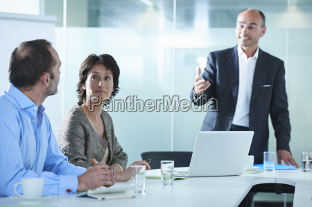 businessmen and women arguing across boardroom