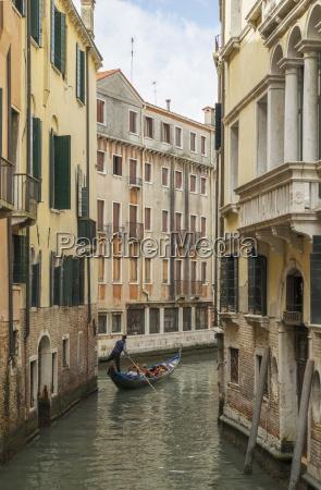 gondolier on narrow canal venice veneto