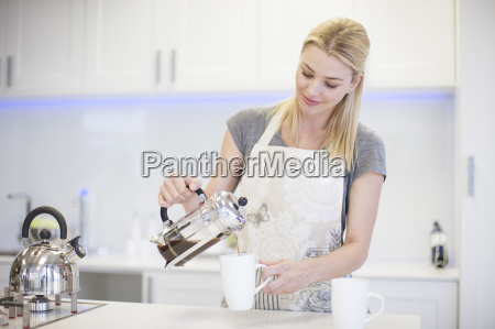 young woman pouring a coffee from
