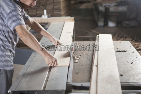 carpenter working with wood plank in