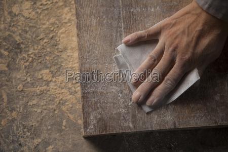 carpenter smoothing surface of wood plank