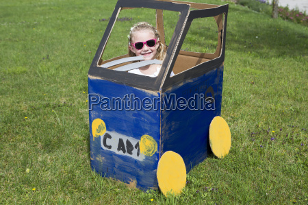 girl playing in homemade toy car