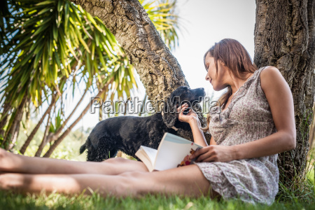 mid adult woman petting dog in
