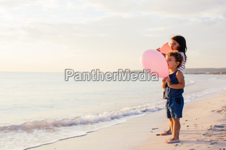 girl and toddler sister with balloons