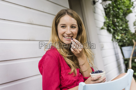 young woman eating blueberries in front