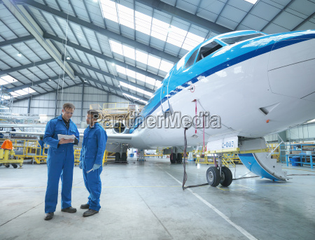 engineers in discussion by aircraft in