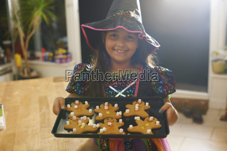 girl wearing halloween witch costume holding