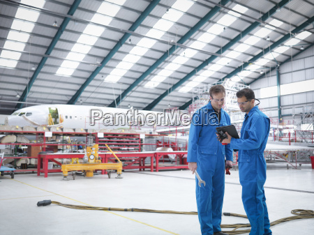 engineers in discussion in aircraft maintenance