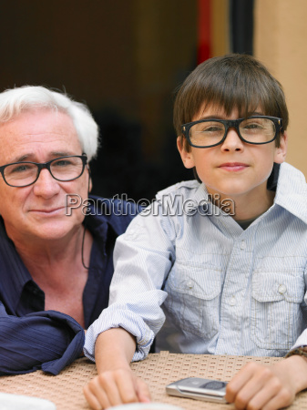 boy and grandfather sitting at cafe