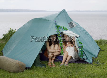 two women looking out from tent