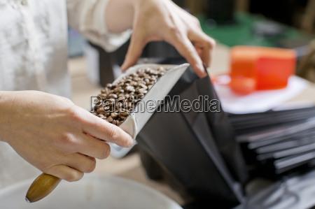 coffee seller filling bag with coffee