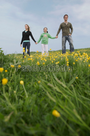parents and child stand on hillside