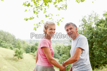 mature couple holding hands looking back