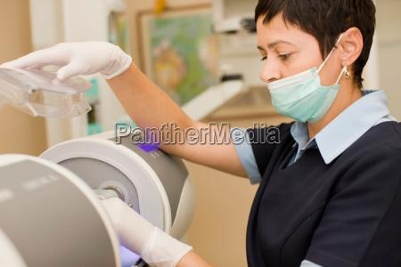 nurse in facemask preparing equipment