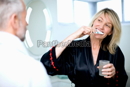woman brushing her teeth in bathroom