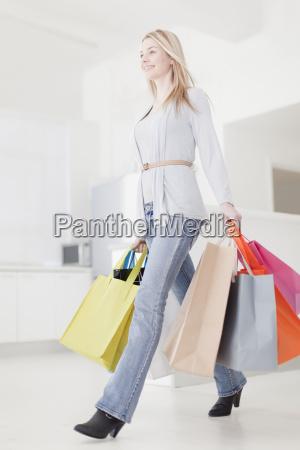 smiling woman carrying shopping bags