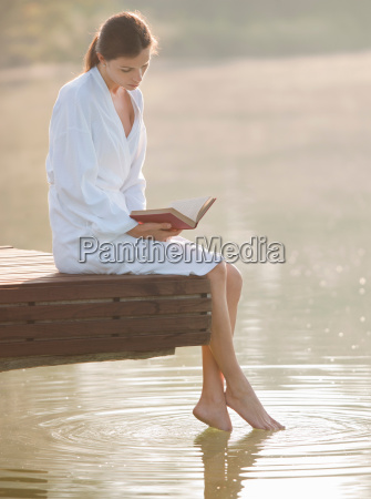 woman reading and dangling feet in
