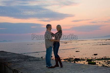 couple hugging on pier at sunset