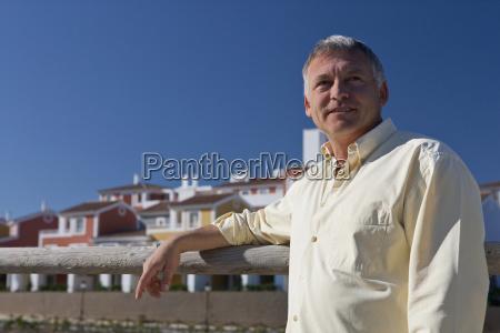 man standing by property development