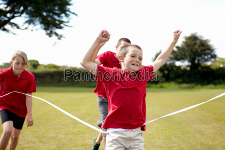 boy cheering and crossing finish line