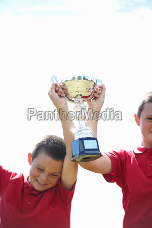 boys cheering with trophy outdoors