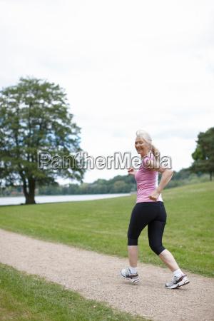 older woman jogging in park