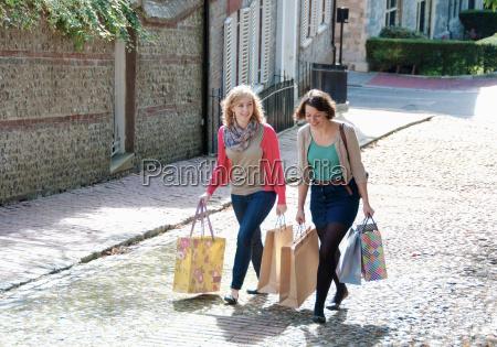 teenage girls carrying shopping bags