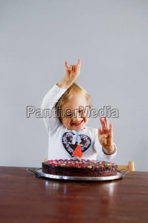 girl cheering with birthday cake