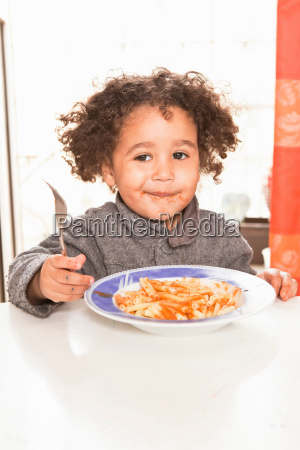 girl eating pasta with sauce at
