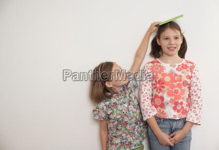 girl measuring taller sister