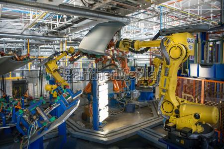 robots handling car parts in car