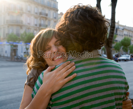 young woman embracing young man