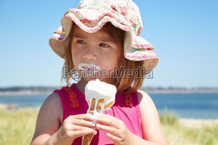 girl eating ice cream on beach