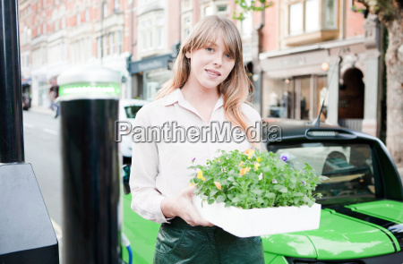 woman carrying flowerbox on city street