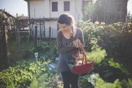 young woman holding basket in garden