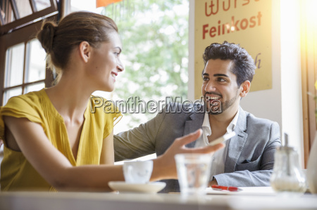 young couple sitting inside cafe talking