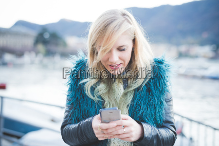 young woman reading smartphone texts at