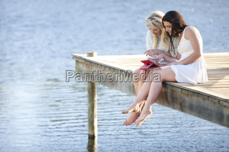 two young women sitting on pier
