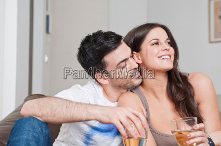 young couple sitting on sofa sharing