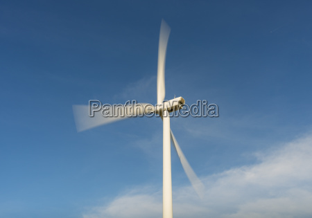 wind turbine in motion against blue