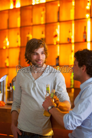 two men standing at bar with