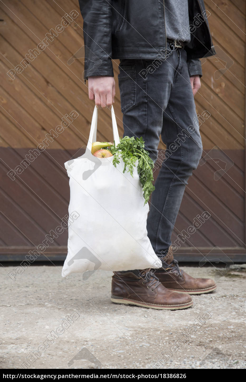teenage, boy, carrying, reusable, shopping, bags - 18386826