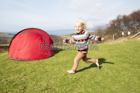 boy running on grass with tent