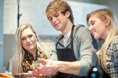 young adults preparing food in kitchen