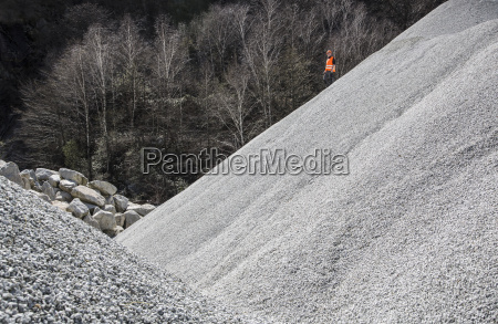 quarry worker on gravel mound at