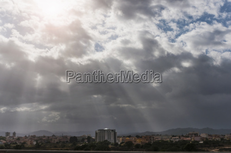 storm cloud with sunbeam over city