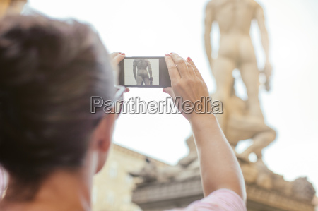 woman photographing replica statue of michaelangelos